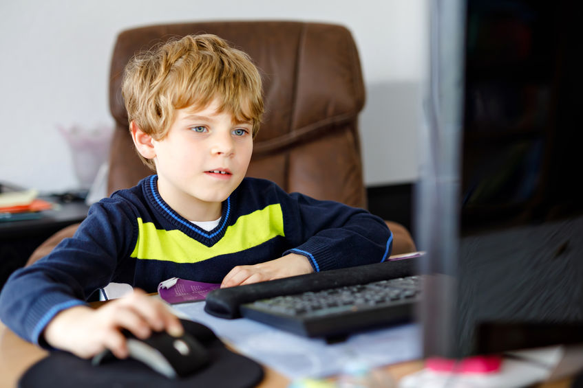 Boy at computer using mouse.